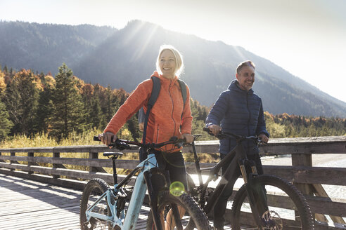 Austria, Alps, couple with mountain bikes crossing a bridge - UUF16594