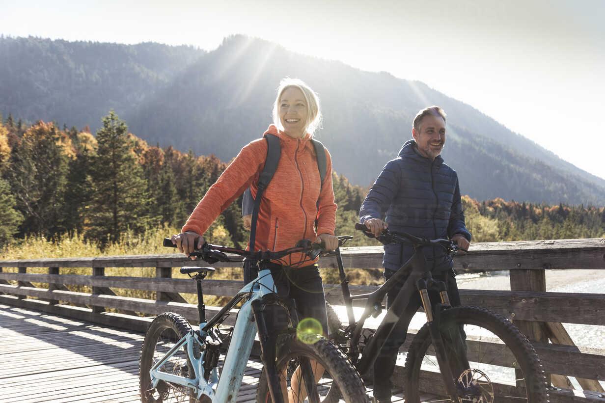 Austria, Alps, couple with mountain bikes crossing a bridge - UUF16594 - Uwe Umstätter/Westend61