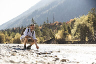 Austria, Alps, man on a hiking trip having a cooling break at a brook - UUF16603