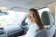Happy woman on passenger seat in car - KIJF02226