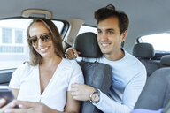 Happy couple in car with man on back seat and woman with cell phone on front passenger seat - KIJF02232