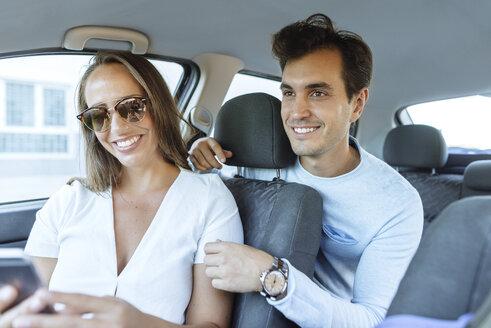 Spain, Andalusia, cadiz, El Puerto de Santa Maria, Couple in car looking at a mobile phone. - KIJF02232