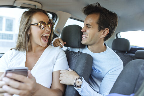 Happy couple in car grimacing with man on back seat and woman on front passenger seat - KIJF02235