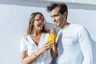 Happy couple sharing an orange juice on a sunny day - KIJF02244
