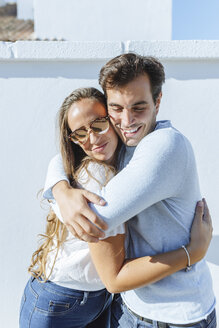 Smiling couple hugging on a sunny day - KIJF02247