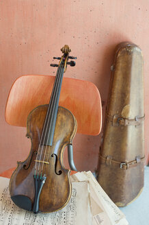 Violin and sheet music on wooden chair with violin case in the background - CRF02814