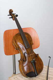 Violin, bow and sheet music on wooden chair, close-up - CRF02817
