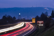Germany, Stuttgart, Warning sign for particulate pollution alert and traffic in the evening - WDF05048