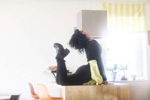 Junge Tänzerin mit Schürze macht eine Tanzfigur in der Küche - SGF02217