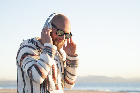 Man with headphones and sunglasses at the beach - KBF00471