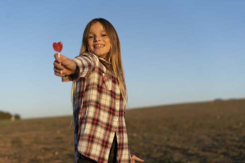 Portrait of smiling blond girl with lollipop at sunset - ERRF00670