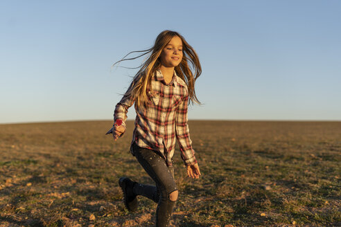 Portrait of smiling girl with lollipop running on pasture by sunset - ERRF00673