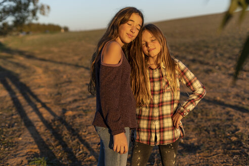 Portrait of two smiling girls enjoying sunset together in nature - ERRF00676