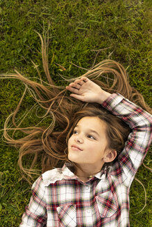 Portrait of smiling girl with long hair lying on a meadow - ERRF00691
