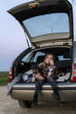 Portrait of girl sitting in opened boot with her dog - ERRF00715