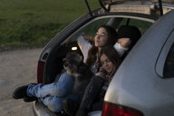 Two sisters in opened boot of parked car watching sunset - ERRF00718