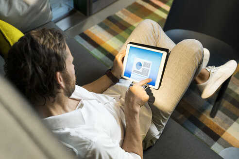 Casual businessman working in lounge area of a coworking space, using digital tablet - SBOF01621
