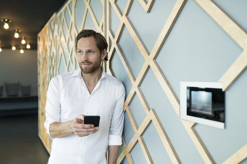Smiling casual business man leaning onto wall in lounge area holding smartphone - SBOF01624