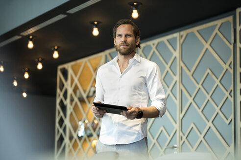 Confident entrepreneur standing in office lounge holding tablet - SBOF01627
