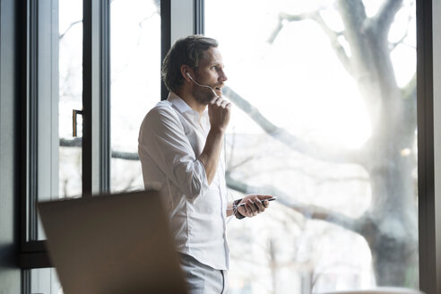 Casual entrepreneur standing in modern office space looking out of window and speaking on smartphone - SBOF01639
