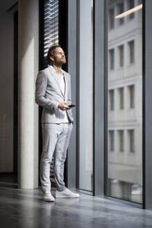 Confident entrepreneur with closed eyes standing in front of window in modern office space holding smartphone - SBOF01642
