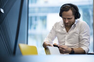 Casual business man with headphones, working on smartphone in modern office - SBOF01651