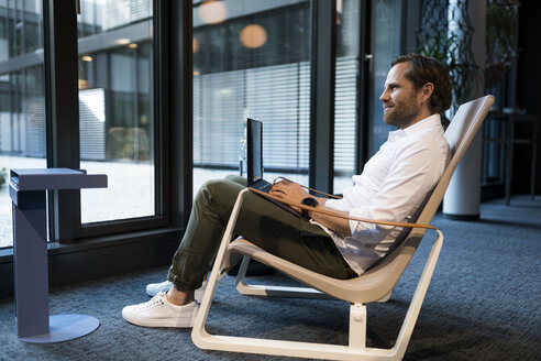 Casual businessman working in lounge area of a coworking space, using laptop - SBOF01654