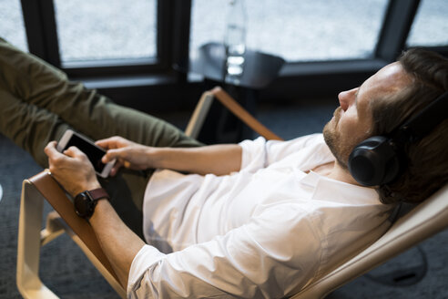 Casual businessman relaxing in lounge area of a coworking space, listening music - SBOF01657