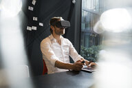 Business man with virtual reality glasses and tablet sitting in modern office - SBOF01666