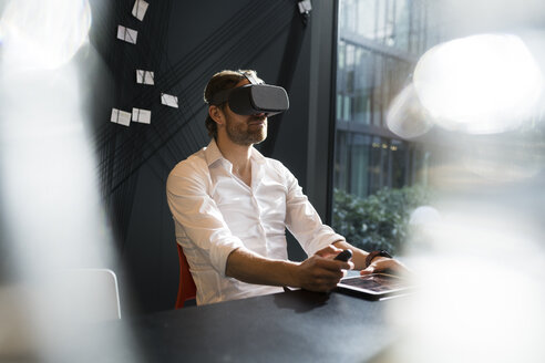 business man with virtual reality VR glasses and tablet sitting in modern office - SBOF01666