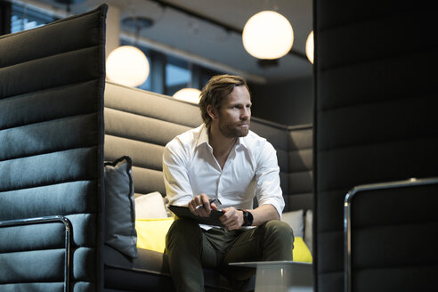 Business man in office lounge area talking to a client - SBOF01672