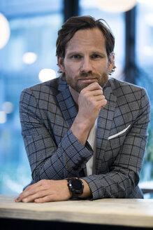Portrait of confident smart entrepreneur in modern office lounge - SBOF01675