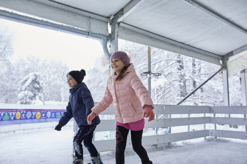 Brother and sister ice skatin on the ice rink - ZEDF01830