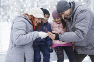 Family with two kids on the ice rink, looking at selfies on their smartphone - ZEDF01833