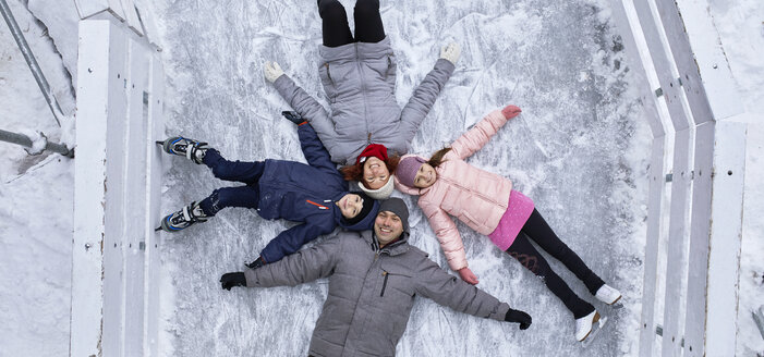 Family with two kids on the ice rink, lying on the ice - ZEDF01845
