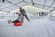 Couple ice skating, using seal sledge to push woman - ZEDF01848