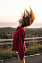 Young woman tossing her hair on country road at sunset - ACPF00398