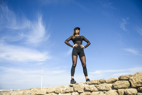 Confident sportive woman standing on stone wall - JSMF00744