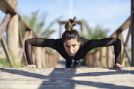Sportive woman doing push-ups on wooden bridge - JSMF00756
