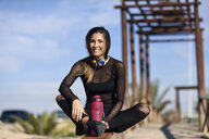 Smiling sportive woman resting after doing sports, sitting on a wooden bridge - JSMF00759