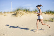 Sportive woman running along sand dunes on the beach - JSMF00768