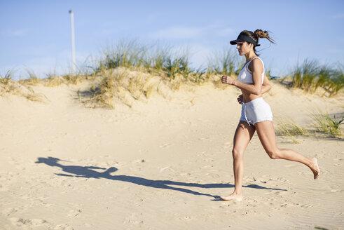 Sportive woman running along sand dunes on the beach - JSMF00768