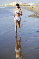 Sportive woman running on the beach - JSMF00771