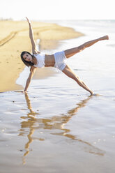 Sportive woman exercising on the beach - JSMF00777