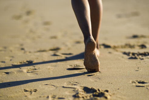 Close-up of woman's feet walking in sand on the beach - JSMF00783
