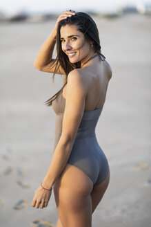Portrait of smiling beautiful woman wearing swimsuit on the beach - JSMF00789