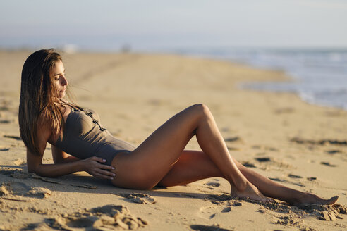 Beautiful woman wearing swimsuit lying on the beach - JSMF00792