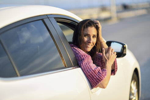 Portrait of smiling woman looking out of car window - JSMF00795