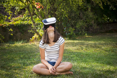 Girl sitting on meadow in the garden using Virtual Reality Glasses - LVF07716