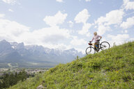 Woman standing with mountain bike on hillside - HEROF08095